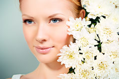 Cosmetics. Close-up portrait of a beautiful blonde girl with white flowers of chrysanthemum. Healthcare. Make-up, cosmetics Stock Image