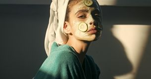 Cosmetics, cosmetology, dermatology. Girl or woman face with cucumber mask. Towel on head. Rejuvenation, health, youth. Skin and hair care, spa, wellness stock images