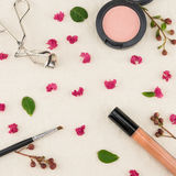 Cosmetics decorated with pink crape myrtle petals. Leaves and budding flowers on muslin fabric stock photography