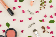 Cosmetics decorated with pink crape myrtle petals. Leaves and budding flowers on muslin fabric stock image