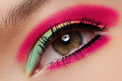 Cosmetics, eyeshadows. Macro fashion eye make-up. Cosmetics and beauty care. Macro close-up of beautiful green female eye with bright fashion make-up. Rainbow stock images