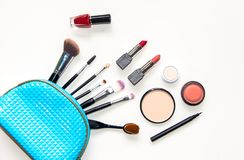 Cosmetics and fashion background with make up artist objects: lipstick, eye shadows, mascara ,eyeliner, concealer, nail polish wit. H blue bag cosmetic royalty free stock image