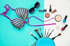 Cosmetics and fashion background with make up artist objects: lipstick, eye shadows, mascara ,eyeliner, concealer, nail polish wit. H summer bikini. Lifestyle royalty free stock photo