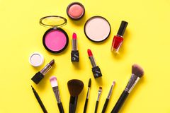 Cosmetics and fashion background with make up artist objects: lipstick, eye shadows, mascara ,eyeliner, concealer, nail polish, ye. Llow colorful background royalty free stock photography