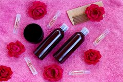 Cosmetics for hair, comb and buds of a red rose on a pink towel royalty free stock image