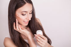 Cosmetics, health and beauty concept - beautiful woman applying cream on her skin Stock Photography