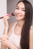 Cosmetics, health and beauty concept - beautiful woman with closed eyes and makeup brush Stock Photo