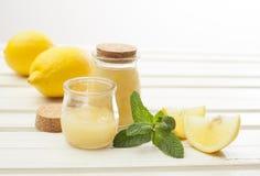 Cosmetics homemade lemon, essential oils, sugar on white wooden. Cosmetics homemade lemon, ginger, salt and essential oils stock photo