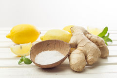 Cosmetics homemade lemon, ginger, salt and essential oils on white wooden table. Cosmetics homemade lemon, ginger, salt and essential oils royalty free stock image