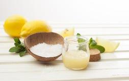 Cosmetics homemade lemon, salt and essential oils on white wooden table. Cosmetics homemade lemon, ginger, salt and essential oils stock photos