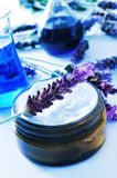 Cosmetics industry. A cream jar and some lavender flowers and flasks in a cosmetics laboratory Stock Photo