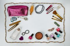 Cosmetics, jewelry, perfumes and a beautiful pink cosmetic bag on a white background, top view stock photography