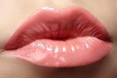 Cosmetics & lips. Macro of fashion lipgloss makeup in sweet kiss royalty free stock photography