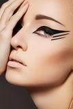 Cosmetics & make-up. Fashion model face, eye liner. Fashion & beauty close-up portrait of attractive young woman model face with beautiful catwalk make-up, black stock photography