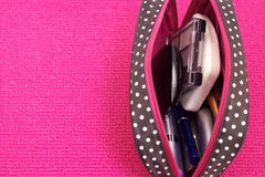 Cosmetics in a makeup bag on a pink background Royalty Free Stock Photos