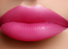 Cosmetics, makeup. Bright lipstick on lips. Closeup of beautiful female mouth with pink lip makeup. Sweet kiss stock photos