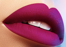 Cosmetics, makeup. Bright lipstick on lips. Closeup of beautiful female mouth with purple lip makeup. Part of face. Cosmetics, makeup and trends. Bright lip stock photo