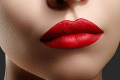 Cosmetics, makeup. Bright lipstick on lips. Closeup of beautiful female mouth with red lip makeup. Clean skin model stock photos