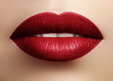 Cosmetics, makeup. Bright lipstick on lips. Closeup of beautiful female mouth with red lip makeup. Part of face. Cosmetics, makeup and trends. Bright lip gloss Royalty Free Stock Photography