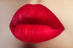 Cosmetics, makeup. Bright lipstick on lips. Closeup of beautiful female mouth with red lip makeup. Valentine sweet kiss royalty free stock image
