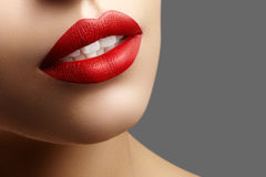 Cosmetics, makeup. Bright lipstick on lips. Closeup of beautiful female mouth with red and pink lip makeup. Part of face royalty free stock photography