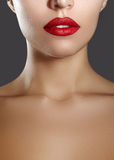 Cosmetics, makeup. Bright lipstick on lips. Closeup of beautiful female mouth with red and red lip makeup. Part of face Royalty Free Stock Photo