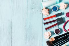 Cosmetics and makeup brushes on vintage blue wooden background, close up stock photography