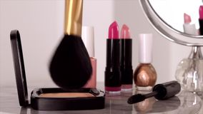 Cosmetics, makeup products on dressing vanity table, lipstick, brush, mascara, nail polish and powder for luxury beauty