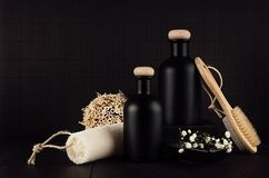 Cosmetics mock up - blank black bottles, bath accessories, white flowers on dark wood board, copy space.
