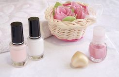 Cosmetics for nail and hands care treatment. Pink and white enamels for French manicure, soap roses Royalty Free Stock Photography