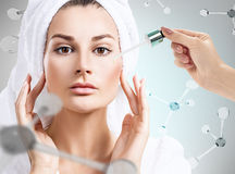 Cosmetics oil on face among the molecules. Young woman with cosmetics oil on face among the molecules. Over gray background. Skin therapy concept Royalty Free Stock Photos