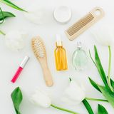 Cosmetics, perfume, combs and tulips flowers on white background. Beauty composition. Flat lay, top view. Cosmetics, perfume, combs and tulips flowers on white Royalty Free Stock Photo