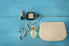 Cosmetics, perfumes, jewelry made of pearls and handbag on an ol Royalty Free Stock Image