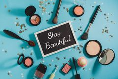 Cosmetics - powder, blush, brushes, mascara, shadows. On a blue background. In the center is a black board with text - Stay  Beautiful Royalty Free Stock Photos