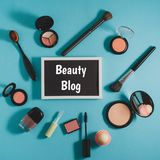 Cosmetics - powder, blush, brushes, mascara, shadows. On a blue background. In the center is a black board for text. Beauty blog concept Stock Image