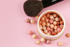 Cosmetics rouge balls in the bank. On a pink background stock image