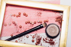 Cosmetics. Scattered shadows, applicator, balls of blush  in a gold frame. Abstraction. Cosmetics. Scattered shadows, applicator, balls of blush and nail polish Stock Photo