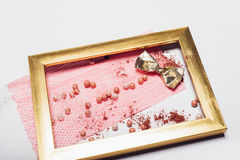Cosmetics. Scattered shadows, applicator, balls of blush  in a gold frame. Abstraction. Cosmetics. Scattered shadows, applicator, balls of blush and nail polish Royalty Free Stock Photos