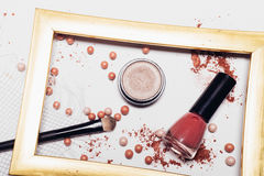 Cosmetics. Scattered shadows, applicator, balls of blush and nail polish in a gold frame. Abstraction. Cosmetics. Scattered shadows, applicator, balls of blush Stock Photography