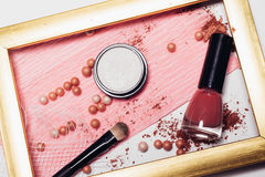 Cosmetics. Scattered shadows, applicator, balls of blush and nail polish in a gold frame. Abstraction. Cosmetics. Scattered shadows, applicator, balls of blush Royalty Free Stock Photography