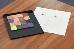 Cosmetics set of different colorful eyeshadow. With paper model face Stock Photos