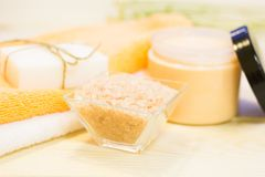 Spa cosmetics set. Cosmetics set- a natural herbal soap, homemade cream, bath salt and with towels, close up. Light wooden background. Spa and body care consept royalty free stock image