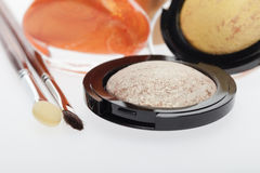 Cosmetics set. With three individual compacts of colorful modern eyeshadow in complimentary colours of beige , yellow and bronze with two small applicators stock photos