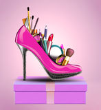 Cosmetics set into a womans shoe standing on gift  Stock Photo