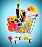 Cosmetics in shopping cart with flowers Stock Photos