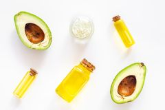 Cosmetics for skin care. Avocado oil near half of avocado on white background top view royalty free stock photography