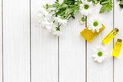 Cosmetics for skin care with chamomile. Oil, soap on white wooden background top view copy space Royalty Free Stock Images