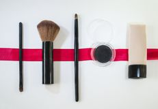 Cosmetics on white background with red ribbon. Makeup brushes and cream and eyeshadows on white background with red ribbon Royalty Free Stock Photos