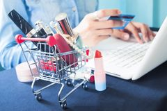 Cosmetics and woman`s essentials in shopping cart with woman usi. Ng laptop and credit card for online shopping Royalty Free Stock Photos