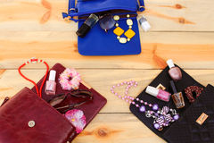 Cosmetics and women's accessories fell out of different handbag. Royalty Free Stock Image
